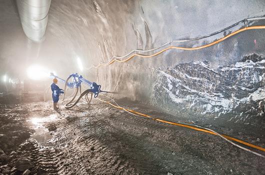 Stavebný robotník strieka betón strojom v tuneli