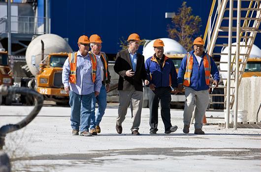 Ryhmä betonin valmistajia rakennustyömaalla. Taustalla: neljä ajoneuvoalustaista betonisekoitinta.