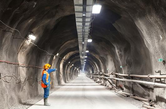 Worker pointing into a tunnel.