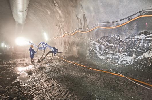 Рабочий распыляет бетон с помощью специальной установки в тоннеле.