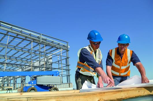 Two contractors working on construction plans