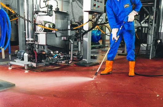 Pracovník čistí podlahu v provozu