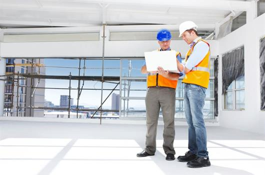 Two men working with a laptop at construction place.