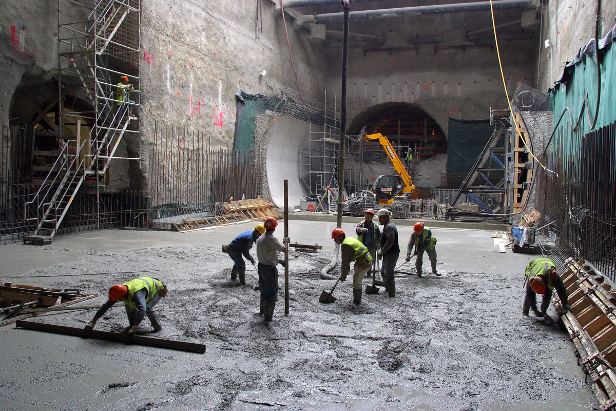 Workers placing concrete at construction site