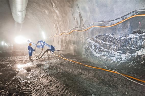 Construction worker spraying of concrete with a machine in a tunnel