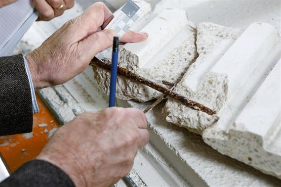 Close-up of two hands inspecting a sample of corroded concrete.