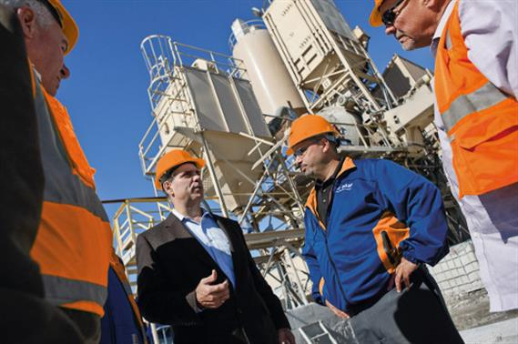 A group of concrete producers walking on a construction site. In the background: four concrete mixer trucks.