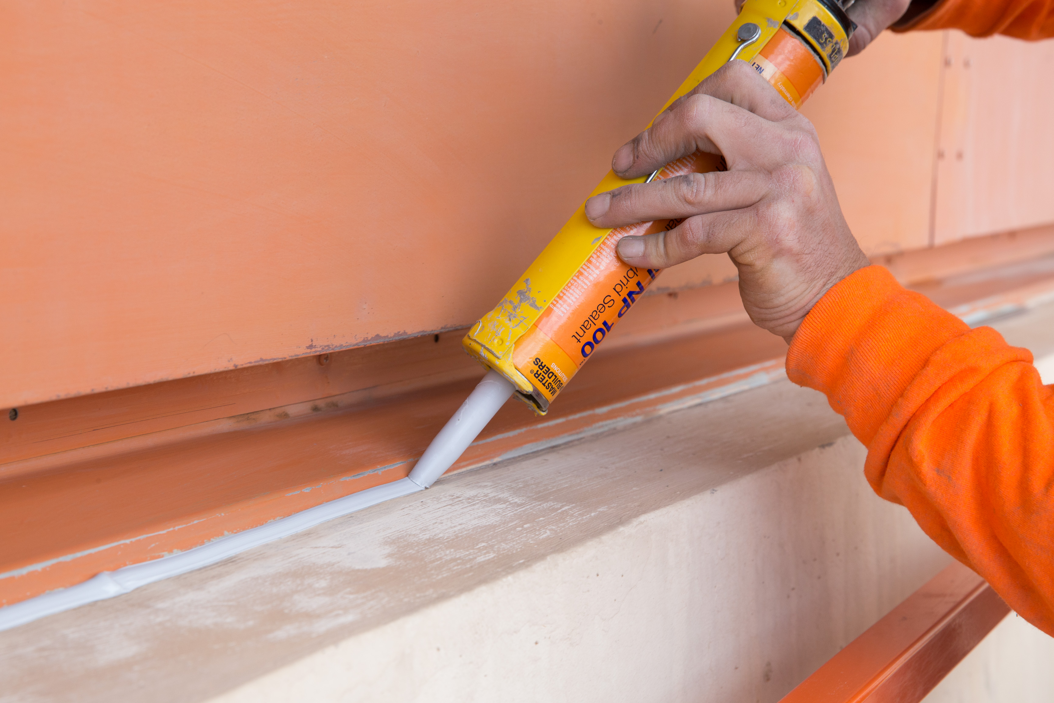 Construction sealant being used to fill an exterior joint.
