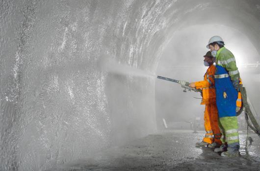 Anleggsarbeidere sprøyter betong i en tunnel