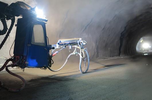 En anleggsarbeider sprøyter betong med en maskin i en tunnel